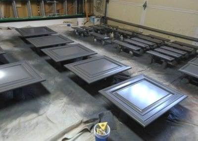 An image of kitchen cabinet doors and drawer fronts layed out in a garage for refinishing