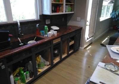 An image of kitchen cabinets without the doors in place