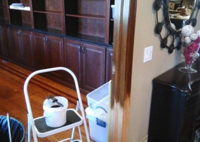 A step ladder with a brush laying on a bucket of stain next to a door frame being stained
